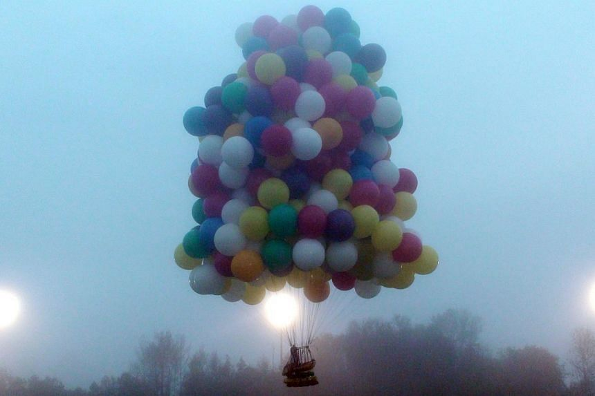 A balloon cluster carrying Mr Jonathan Trappe lifts off from Caribou, Maine, on Sept 12, 2013, in this photo provided by Mr Mark McBreairty. In a scene reminiscent of the Pixar movie Up, Mr Trappe set off on Thursday in a daring bid to drift across t