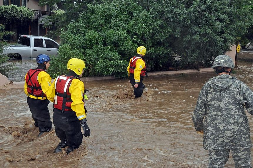 In this photo provided by the Colorado National Guard, guardsmen, including water rescue specialists in red vests, search a flooded neighbourhood in Lyons, Colorado, on Sept 12, 2013. The United States National Guard drove military vehicles into a sm