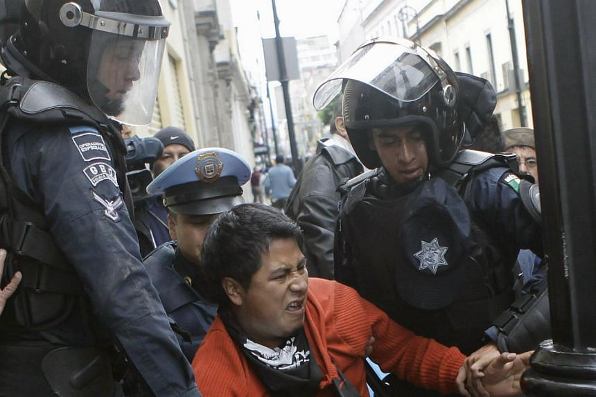 A protester (centre) is arrested by the riot police during clashes as striking members of the teachers' union CNTE are evicted from Zocalo Square in downtown Mexico City on Sept 13, 2013. Anti-riot police stormed Mexico City's historic centre to remo