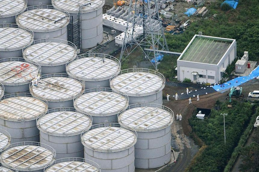 An aerial view shows workers wearing protective suits and masks working atop contaminated water storage tanks at crippled Fukushima Daiichi nuclear power plant in Fukushima.Japan's nuclear authority plans to conduct radiation contamination surv