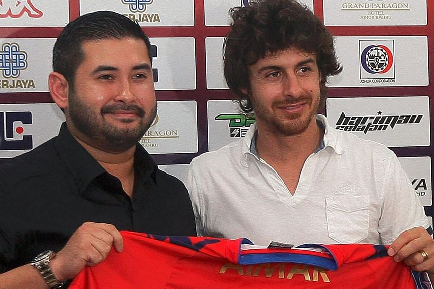 Former Argentina national squad football player Pablo Aimar (right) holds up his new jersey with president of the Johor Darul Takzim football club, Mr Tengku Ismail, after signing a contract with Malaysian club Johor Darul Takzim on Saturday. Th