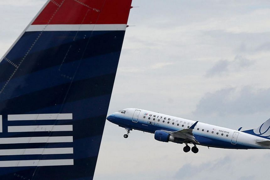 A United Airlines jet takes off behind a US Airways jet at Ronald Reagan Washington National Airport on Aug 13, 2013 in Arlington, Virginia. Some lucky customers who acquired United Airlines tickets at zero cost because of a computer programming erro