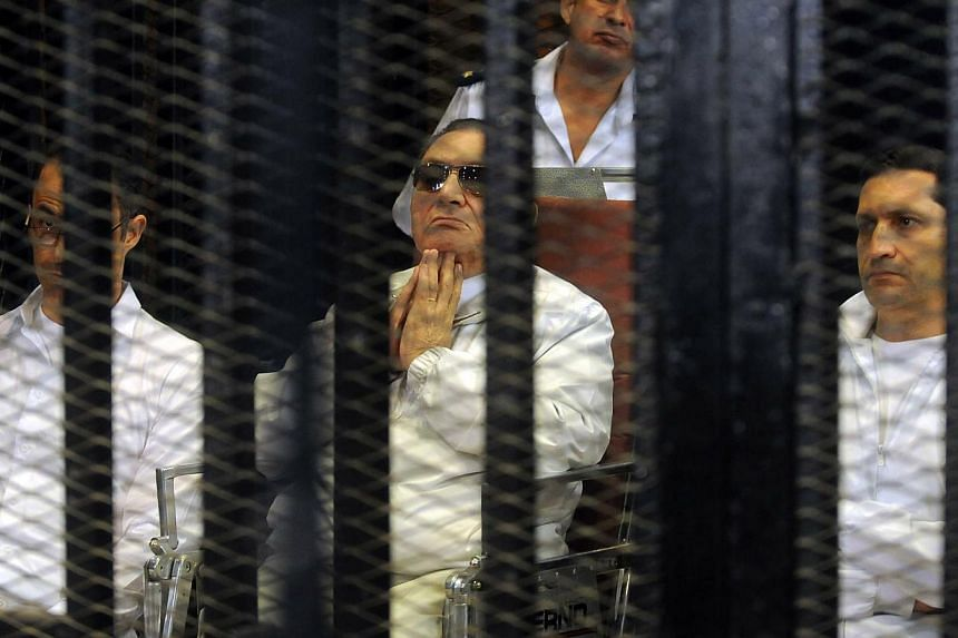 Former Egyptian president Hosni Mubarak (centre) and his sons Gamal (left) and Alaa (right) are seen behind bars on Aug, 25 2013 in Cairo, Egypt.An Egyptian court on Saturday resumed the trial of the toppled dictator, who is accused of co
