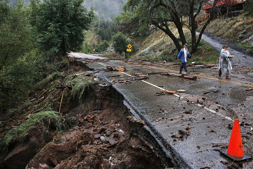 Brother and sister Patrick Tinsley and Mary Kerns walk into Boulder, Colorado., from their mountain community Magnolia, where road access is shut off by debris from days of record rain and flooding, at the base of Boulder Canyon, Colorado, on Friday