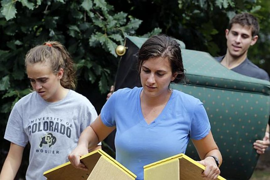 University of Colorado students carry belongings to an apartment in Boulder, Colorado, on Sept 13, 2013. Floodwaters cascaded downstream from the Colorado Rockies on Friday, spilling normally scenic mountain rivers and creeks over their banks and for