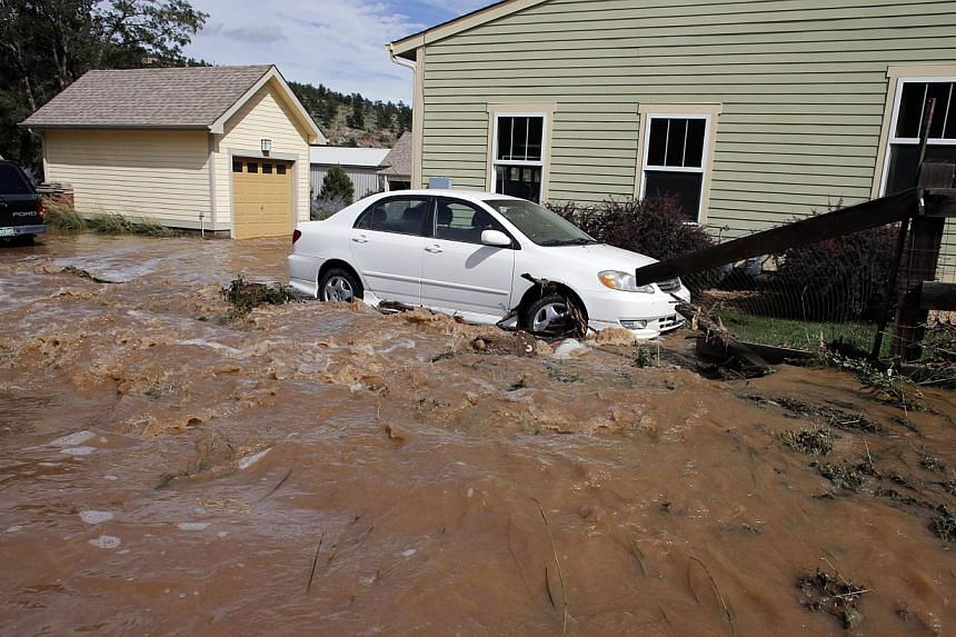 Water rushes through a neighbourhood in Lyons, Colorado, on Sept 13, 2013. Days of heavy rains and flash floods which washed out all the town's bridges have left Lyons residents stranded from emergency crews, and has sectioned off the town into sever