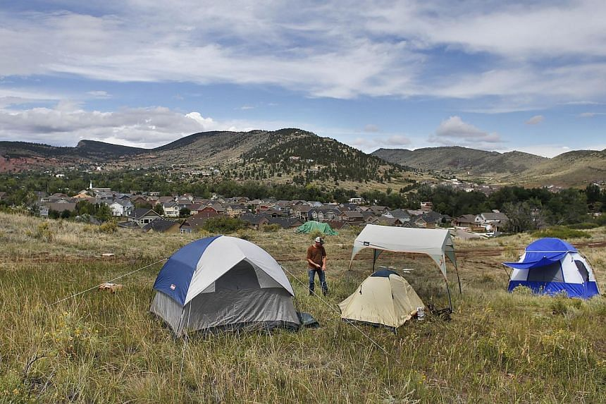 Temporarily displaced Lyons resident Kevin Bonner walks among a makeshift camp for people who voluntarily camped on higher ground due to fears of a dam breaking, on a hill overlooking Lyons, Colorado, on Sept 13, 2013. Days of heavy rains and flash f