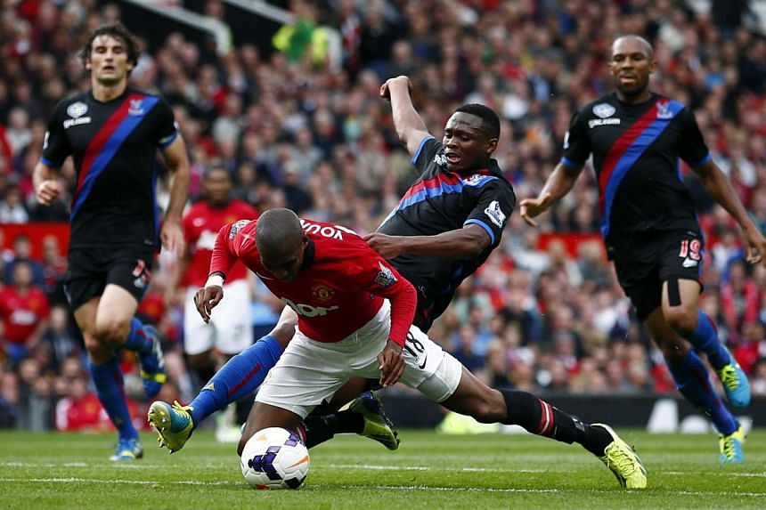 Manchester United's Ashley Young (left) is fouled by Crystal Palace's Kagisho Dikgacoi during their English Premier League soccer match at Old Trafford in Manchester, northern England Sept 14, 2013. Manchester United manager David Moyes has admitted
