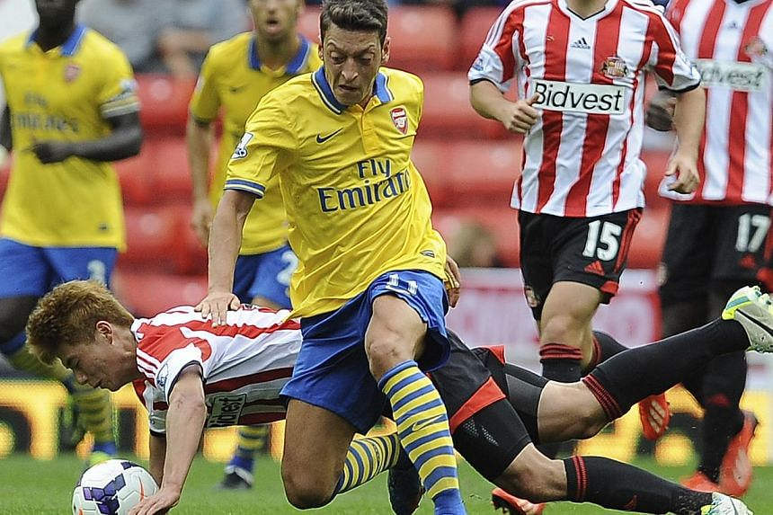 Arsenal's Mesut Ozil (C) is challenged by Sunderland's Ki Sung-Yeung (L) during their English Premier League soccer match at The Stadium of Light in Sunderland, northern England, September 14, 2013.Aaron Ramsey's double helped Arsenal's club re