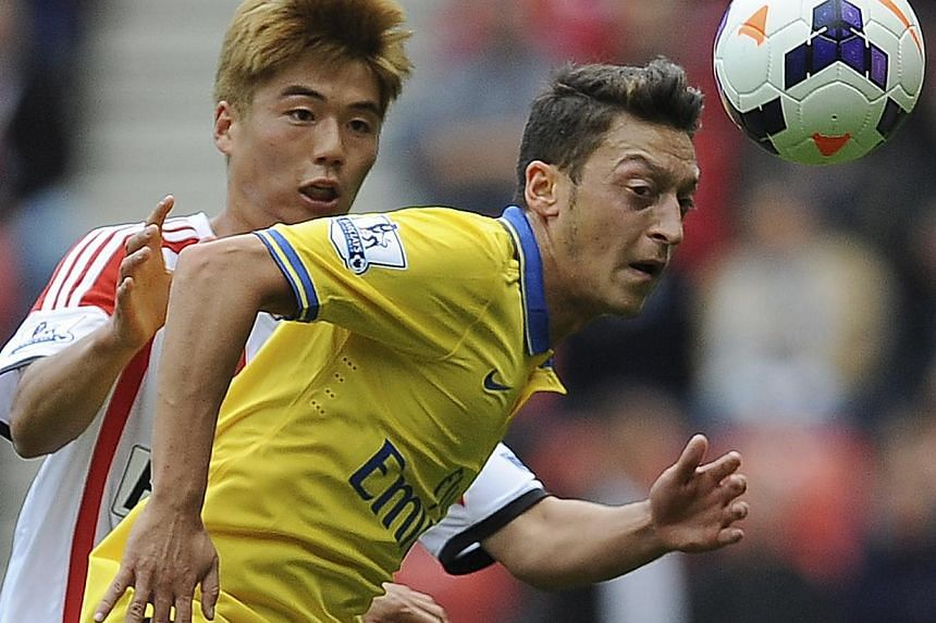 Arsenal's Mesut Ozil (right) is challenged by Sunderland's Ki Sung-Yeung during their English Premier League soccer match at The Stadium of Light in Sunderland, northern England, Sept 14, 2013. Arsene Wenger revealed he took a gamble in handing a Pre
