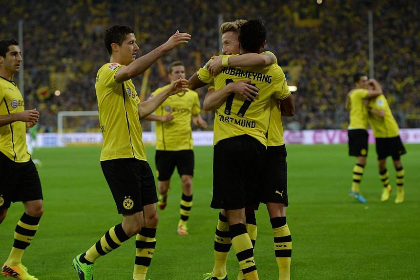 Dortmund's Polish striker Robert Lewandowski (2ndL), Dortmund's striker Marco Reus and Dortmund's Gabonese striker Pierre-Emerick Aubameyang celebrate after winning the German first division Bundesliga football match Borussia Dortmund vs Hamburger SV