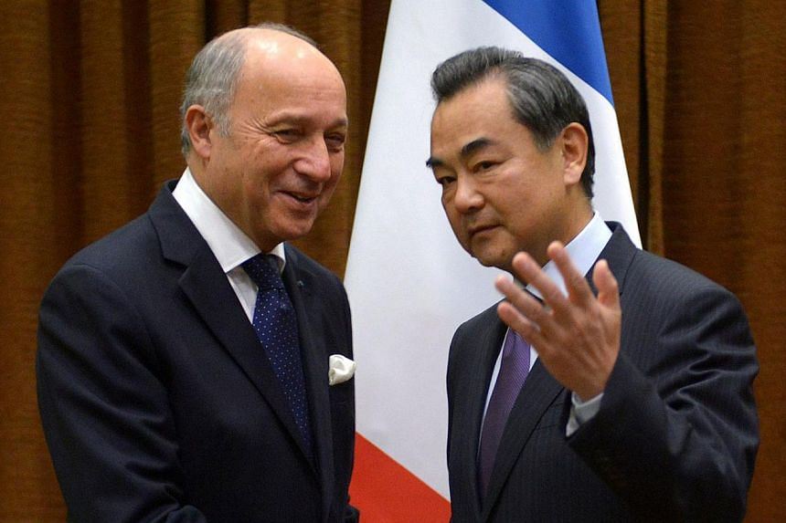 French Foreign Minister Laurent Fabius (left) shakes hands with Chinese Foreign Minister Wang Yi (right) before their meeting at the Chinese Foreign Ministry in Beijing on Sept 15, 2013. China's foreign minister on Sunday welcomed the deal between th