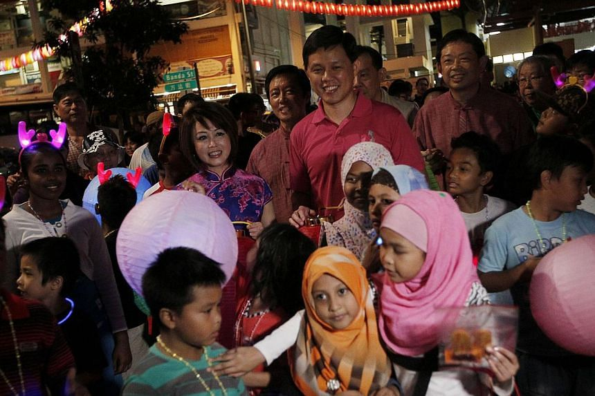 Minister for Social and Family Development Chan Chun Sing (background centre) and Tanjong Pagar GRC MP Dr Lily Neo (left), walk with children carrying lanterns during the Chinatown Mid-Autumn Festival 2013 Mass Lantern Walk on Sept 15, 2013.
