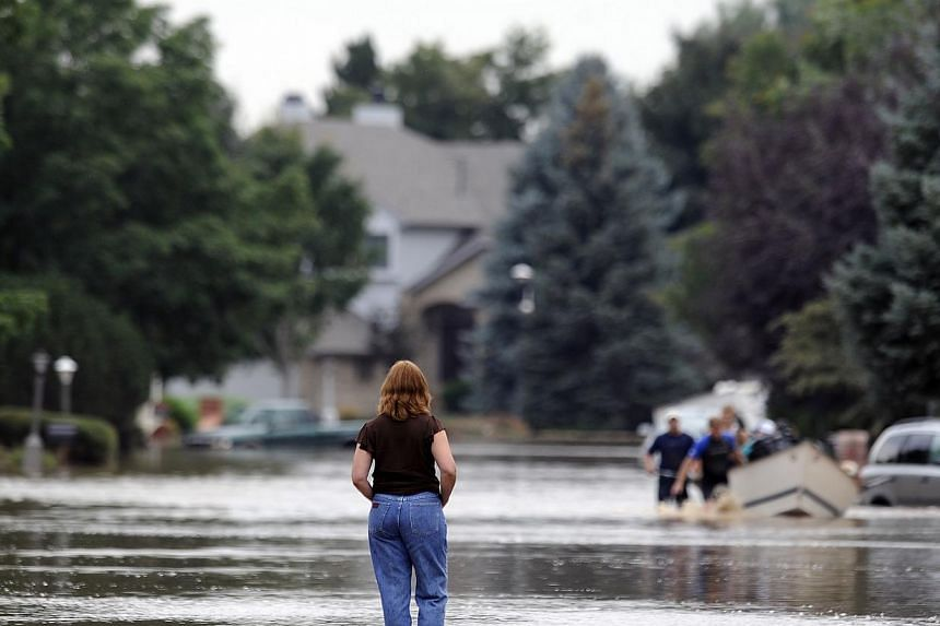 A resident watches a boat float down the centre of the street in Longmont, Colorado, on Saturday, Sept 14, 2013. Floodwaters have affected a 11,655 sq km section of the state. National Guard helicopters have been evacuating residents from the hardest