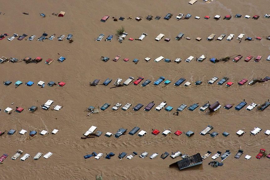 A field of parked cars and trucks sits partially submerged near Greeley, Colorado, Saturday, Sept. 14, 2013, as debris-filled rivers flooded into towns and farms miles from the Rockies. Hundreds of roads, farms and businesses in the area have been da