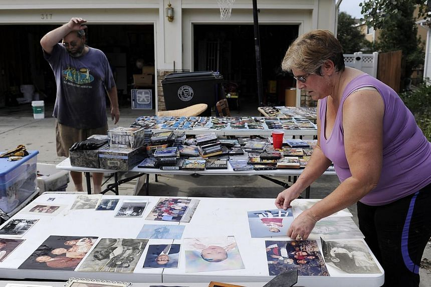 Krsitin McDonald, right, dries out family photos while her husband Stanley McDonald, left, wipes his brow after their basement flooded in Longmont, Colorado, on Saturday, Sept. 14, 2013. Floodwaters have affected a11,655 sq kmsection of t