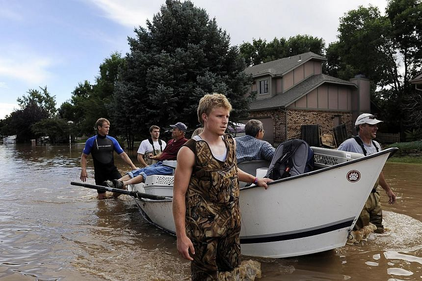 Brian Winn, rear left, Mitch Machmuller, rear center, Eric Machmuller, front centre, and Pat Machmuller, right, steer a boat down a residential street to help residents gather pets and belongings from their flooded homes in Longmont, Colorado, on Sat