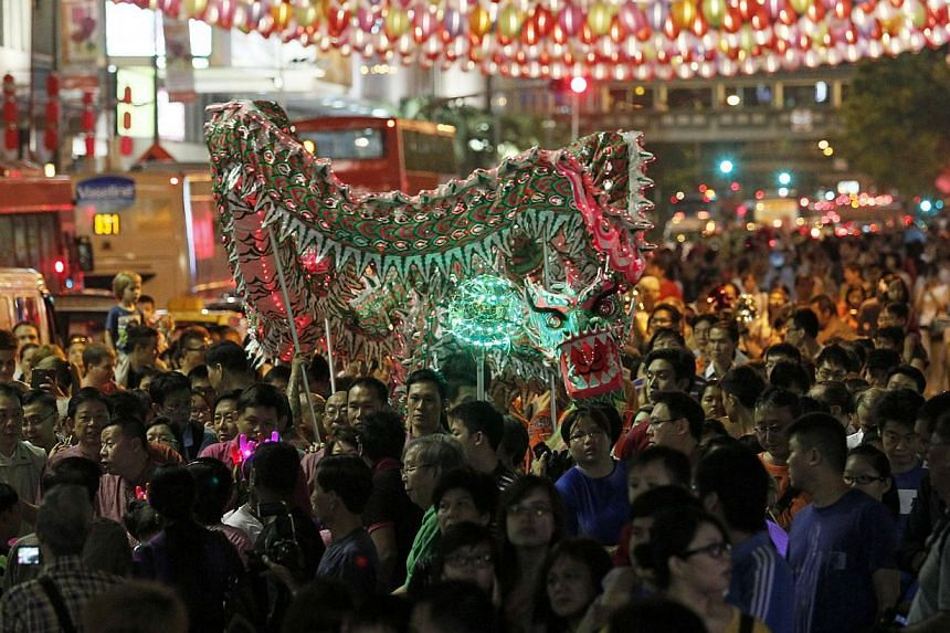 Dragon dancers carrying a dragon pass through participants carrying lanterns during the Chinatown Mid-Autumn Festival 2013 Mass Lantern Walk on Sept 15, 2013. Thousands gathered in Chinatown on Sunday night to celebrate the Mid-Autumn Festival, which