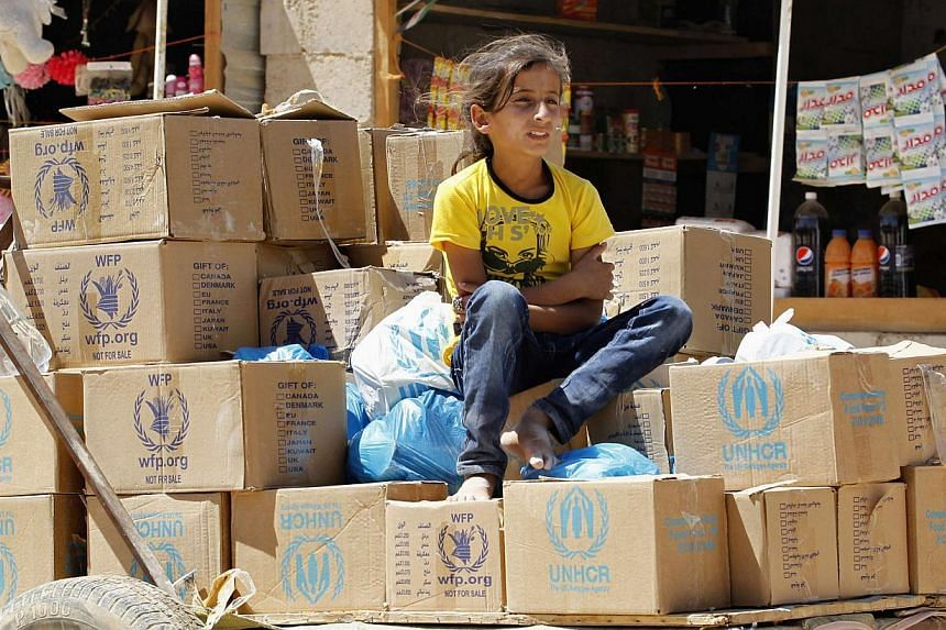 A Syrian refugee girl sits on humanitarian aid boxes, received by her father at Al Zaatri refugee camp in the Jordanian city of Mafraq, near the border with Syria, Sept 8, 2013. More than 2,100 Syrian officers have fled to Jordan since the start of t