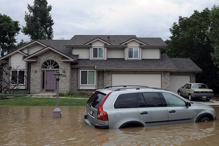A car is surrounded floodwaters in front of a home in Longmont, Colorado, on Saturday, Sept 14, 2013. US emergency workers were rescuing residents of Boulder, Colorado Saturday after floods devastated homes and businesses, reportedly leaving hundreds