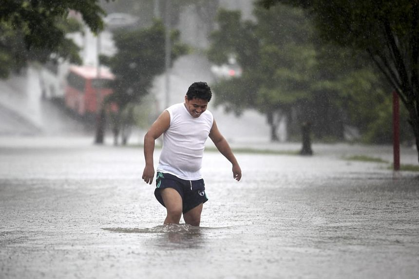 A man walks through a flooded street during heavy rains caused by Tropical Storm Ingrid in the Gulf port city of Veracruz, Mexico, Friday Sept 13., 2013.Ingrid became the second hurricane of the 2013 season on Saturday, US forecasters said, wit
