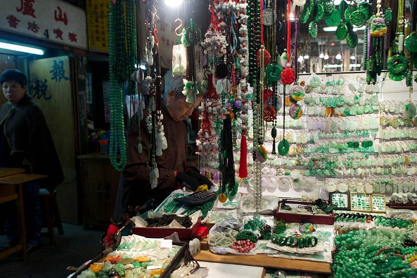 A woman (centre) tending to her stall selling jade jewellery, trinkets and charms at the historic Jade Market near Temple Street in Kowloon, Hong Kong on. -- FILE PHOTO: AFP