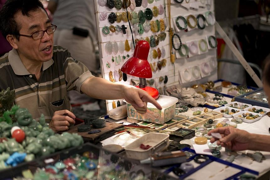 A vendor (left) talking with a customer about a piece of jade at his stall selling jade jewellery, trinkets and charms at the historic Jade Market near Temple Street in Kowloon, Hong Kong. -- FILE PHOTO: AFP