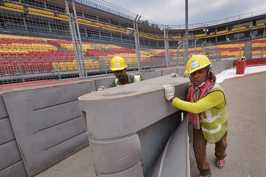 Workers set up barriers at Turn 1 of the Singapore GP race route. Only limited tickets to the SingTel Singapore Grand Prix are available with just six days to go and organisers say they have already exceeded last year's total attendance of 84,31
