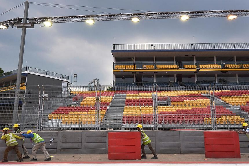 Workers set up barriers at Turn 1 of the Singapore GP race route. The machines have arrived. So too most of the estimated 500 tonnes of equipment. -- ST PHOTO: MUGILAN RAJASEGERAN