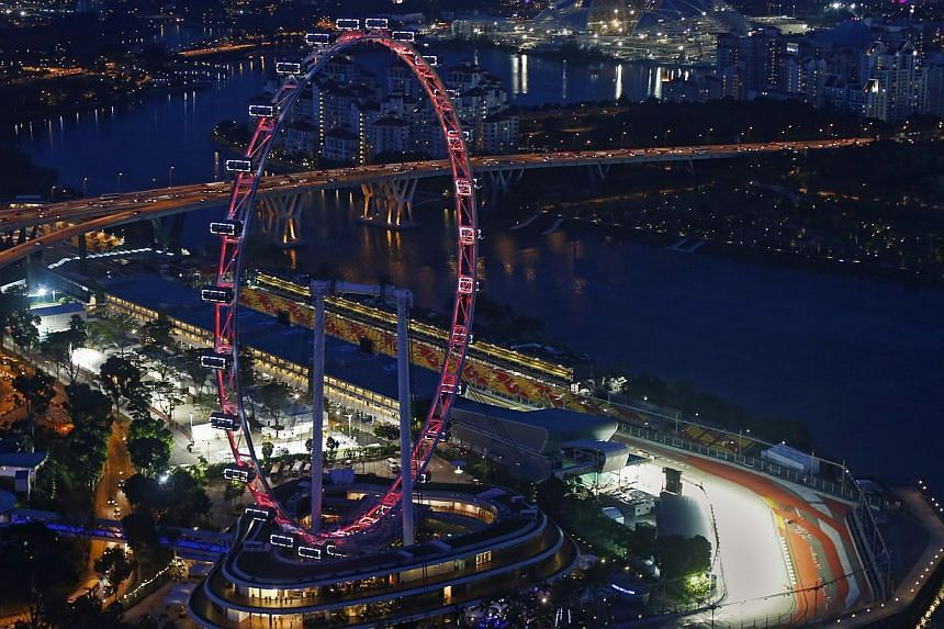 An aerial view shows the main grand stand and the Formula One pit building behind the Singapore Flyer observation wheel at dusk September 11, 2013.But even as Singapore awaits the roar of the Formula One cars' 2.4-litre V8 engines later this we