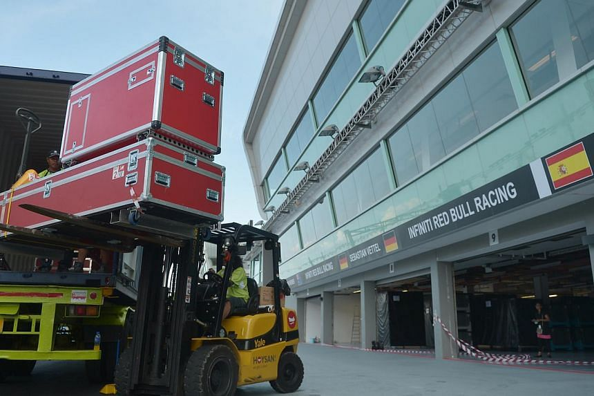 Workers transporting equipment from containers in prepartion for next week's Formula One Singapore Grand Prix.  Even non-trackside facilities have been getting in on the act. -- PHOTO: CAROLINE CHIA