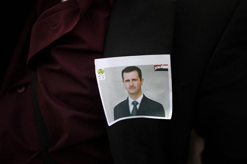 A protester loyal to the Shi'ite Muslim Al-Houthi group, also known as Ansarullah, wears a photo of Syria's President Bashar al-Assad as he demonstrates to show his support for al-Assad, in Sanaa September 13, 2013. Jihadists and members of hard