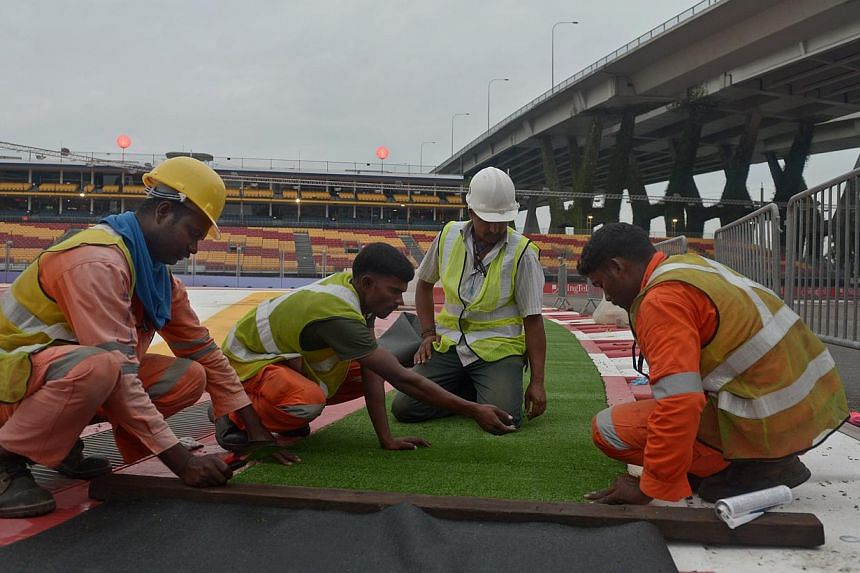Workers laying AstroTurf, or artificial turf, along turn 1 of the track, 15 September 2013.The race was won by Vettel, and it began a remarkable four-race resurgence for the German, which ended in his beating Alonso to the world title by a mere