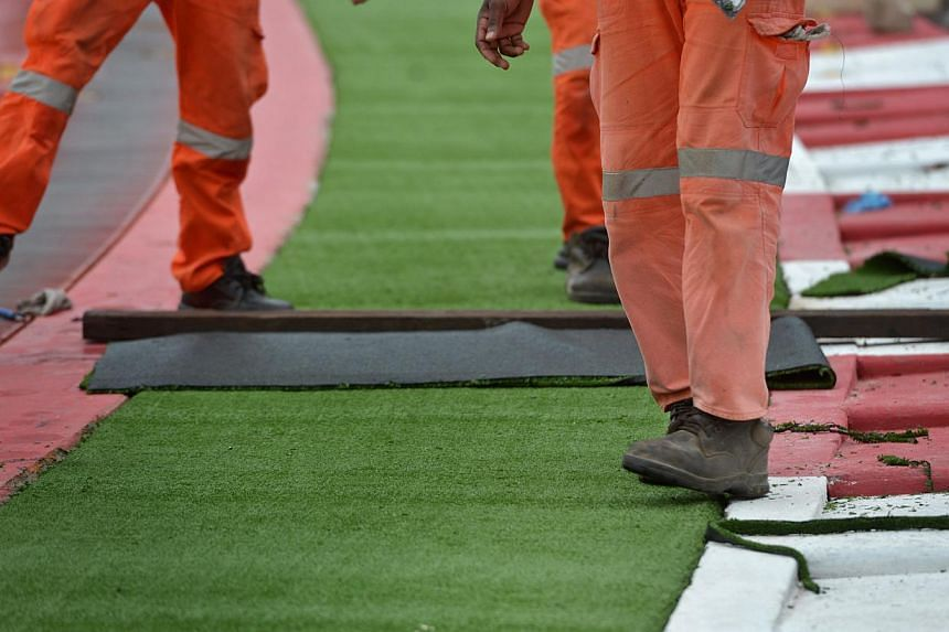 Workers stepping on the freshly laid AstroTurf, or artificial turf, to set it in place, 15 September 2013.But even as Singapore awaits the roar of the Formula One cars' 2.4-litre V8 engines later this week, and last-minute touches are put on the Mari