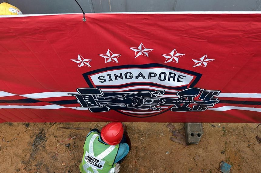 A worker secures the base of an F1 banner, 15 September 2103.Some say that the novelty of having a night race, in the narrow confines of a city, has faded. -- ST PHOTO: CAROLINE CHIA