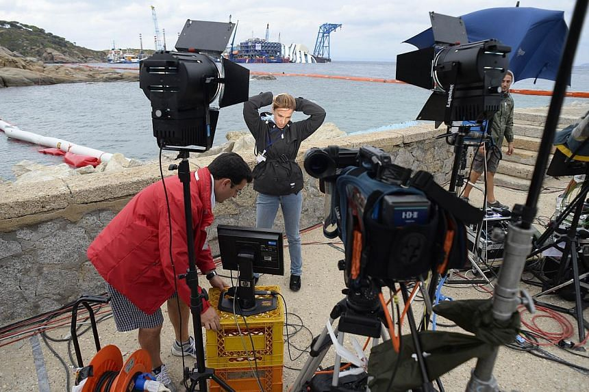Journalists wotk in front of the wreck of Italy's Costa Concordia cruise ship near the harbour of Giglio Porto on September 15, 2013.Once the Costa Concordia is upright, the plan is to stabilise it, refloat it and then tow it away for scrapping in a