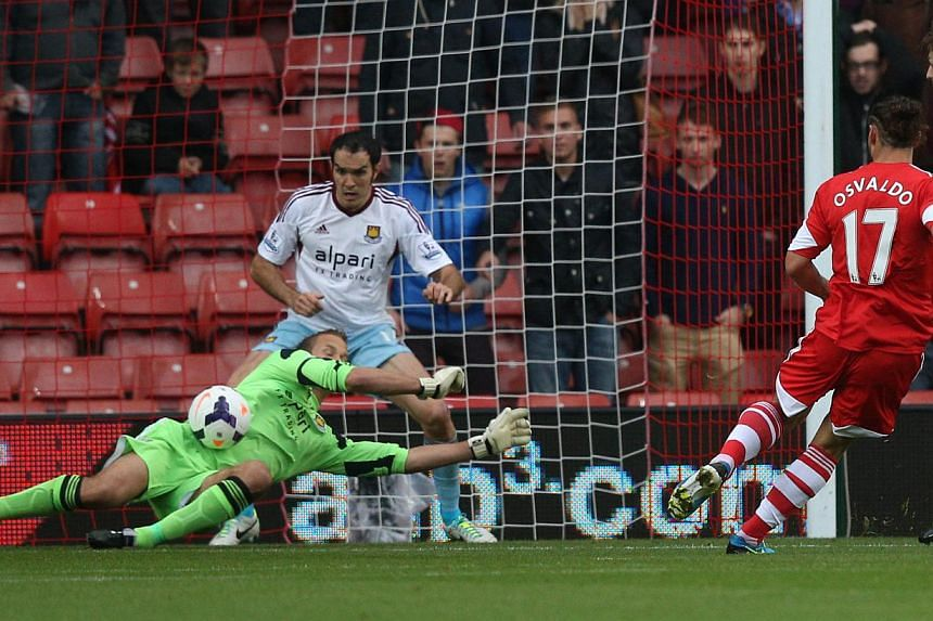 West Ham United's Finnish goalkeeper Jussi Jaaskelainen (left) dives across his goal to save a shot from Southampton's Argentinian-born Italian striker Dani Osvaldo (2R) during English Premier League football match between Southampton and West Ham Un