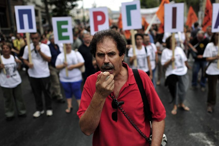 A Greek school teacher shouts slogans as he leads demonstrators marching in central Athens on Monday, Sept 16, 2013. -- PHOTO: AFP