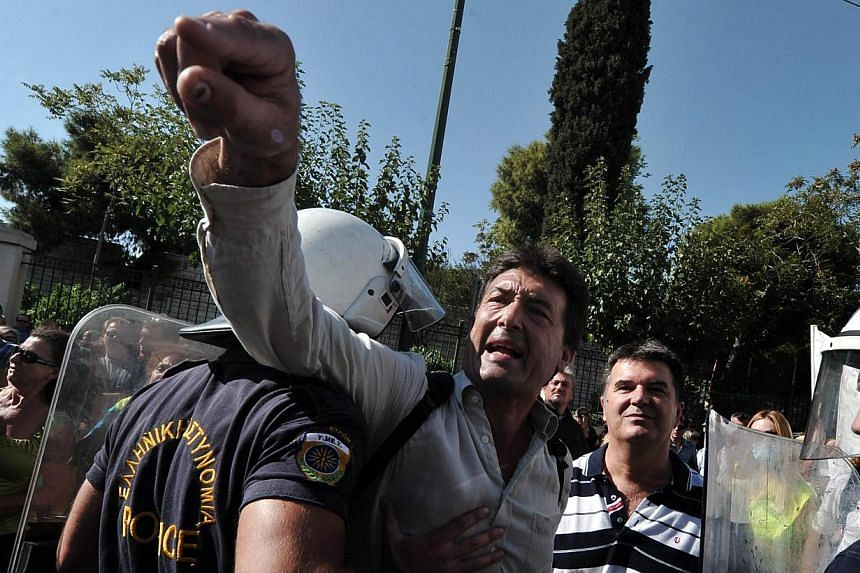 Greek policemen restrain a protester as school guards demonstrate outside the Ministry of Administrative Reform in Athens against their mandatory suspensions on Monday, Sept 16, 2013.Greek police fired tear gas to disperse dozens of school guar