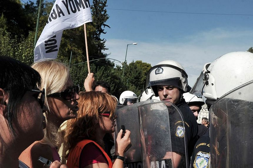 Greek policemen stand opposite school guards demonstrating outside the Ministry of Administrative Reform in Athens against their mandatory suspensions on Monday, Sept 16, 2013. -- PHOTO: AFP