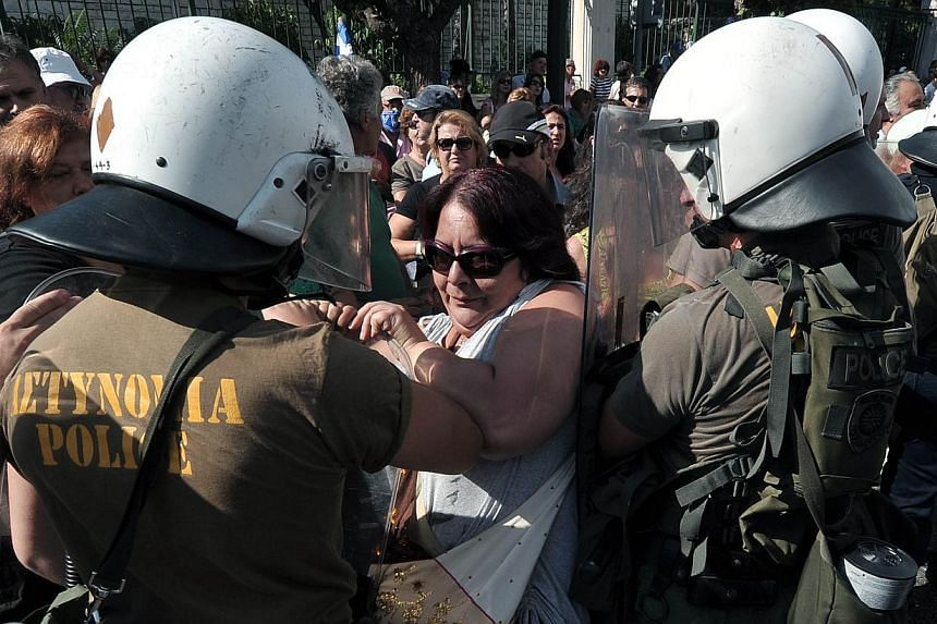 Police push back school guards protesting outside the Ministry of Administrative Reform in Athens against their mandatory suspensions on Monday, Sept 16, 2013. -- PHOTO: AFP