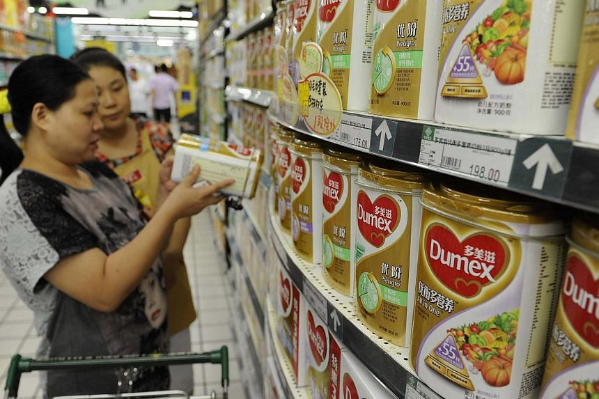 "A sales assistant (back) helps a customer to select Dumex milk powder at a supermarket in Hefei, Anhui province on Aug 5, 2013. Danone's Dumex brand is ""extremely shocked"" by allegations on Chinese state television that it bribed hospital staff"