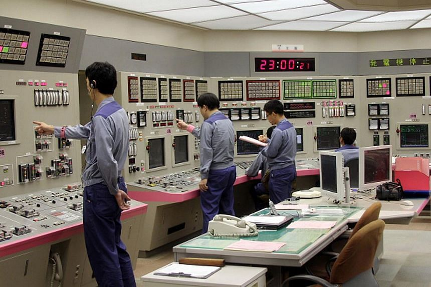This handout picture taken by Kansai Electric Power Co (Kepco) on Monday, Sept 15, 2013 shows Kepco engineers shutting down its nuclear reactor at the company's Oi nuclear power plant in Oi, Fukui prefecture, western Japan. Japan went nuclear-fr