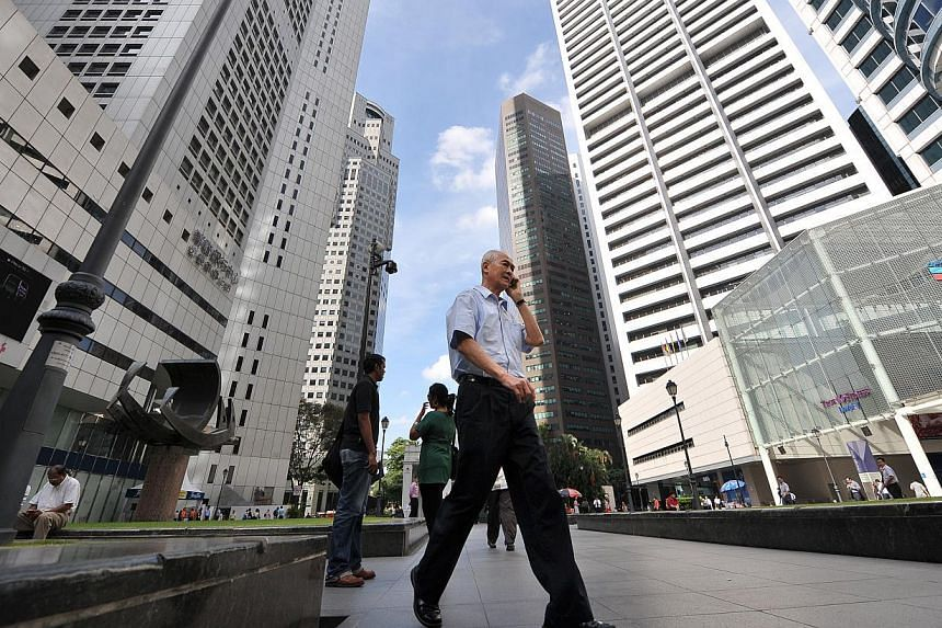 People walking along Raffles Place. Average rents of prime office space rose for the first time since the third quarter of 2011, with more tenants looking for top office spaces. -- ST FILE PHOTO: ALPHONSUS CHERN