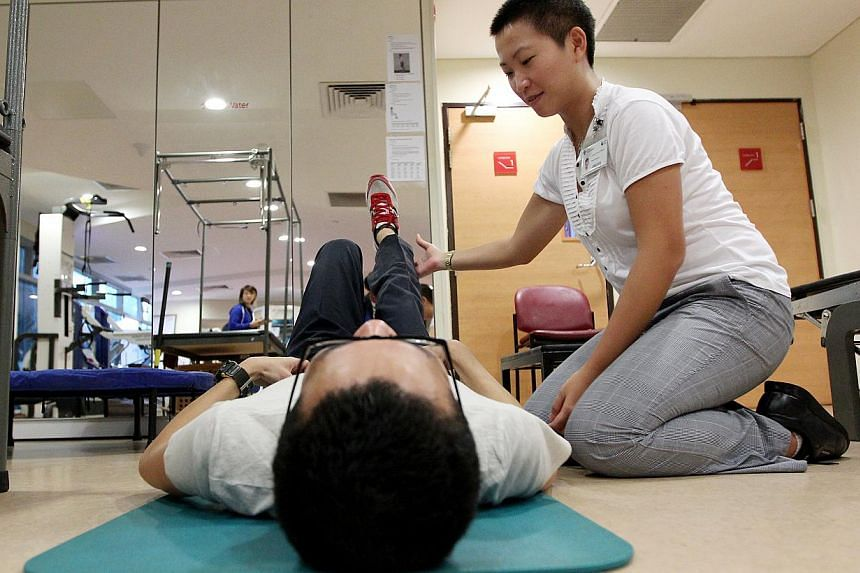 Physiotherapist Philene Leow assisting a patient during an exercise session at the Changi Sports Medicine Centre last Tuesday. Physiotherapists working with patients at Changi Sports Medicine Centre's gym and exercise area last Tuesday. After the exp