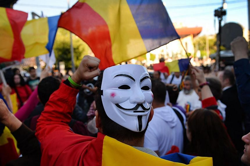A man wears a Guy Fawkes mask as protesters demonstrate in Bucharest against the Rosia Montana Gold Corporation (RMGC), a Canadian gold mine project using cyanide, on Sept 15, 2013. Some 20,000 Romanians took to the streets on Sunday protesting again