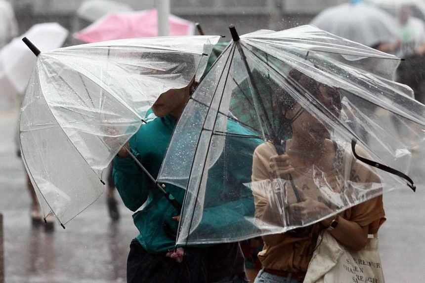 Pedestrians walk against strong wind and rain in Tokyo on Sept 16, 2013. -- PHOTO: AFP