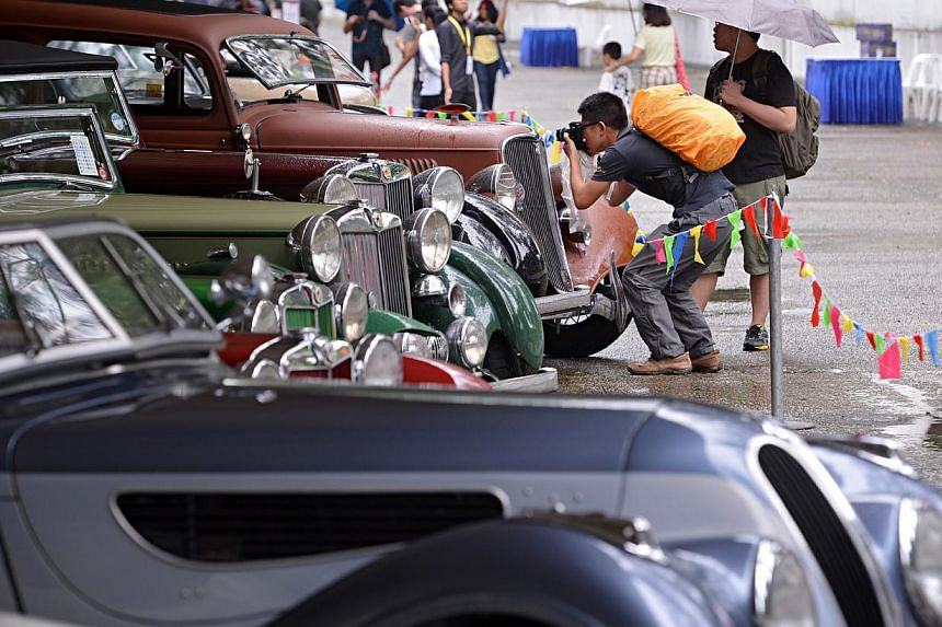 A visitor takes a photo of vintage cars on display at the Motoring Heritage Day where 50 vintage cars and 10 restored bicycles were on show at Tanjong Pagar Railway Station. -- ST PHOTO: NURIA LING