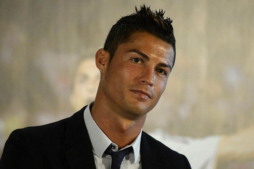 Real Madrid's Portuguese forward Cristiano Ronaldo smiles after signing the renewal of his contract at Santiago Bernabeu in Madrid on Sept 15, 2013. Cristiano Ronaldo believes putting pen to paper on a new Real Madrid deal, which ties him to the club