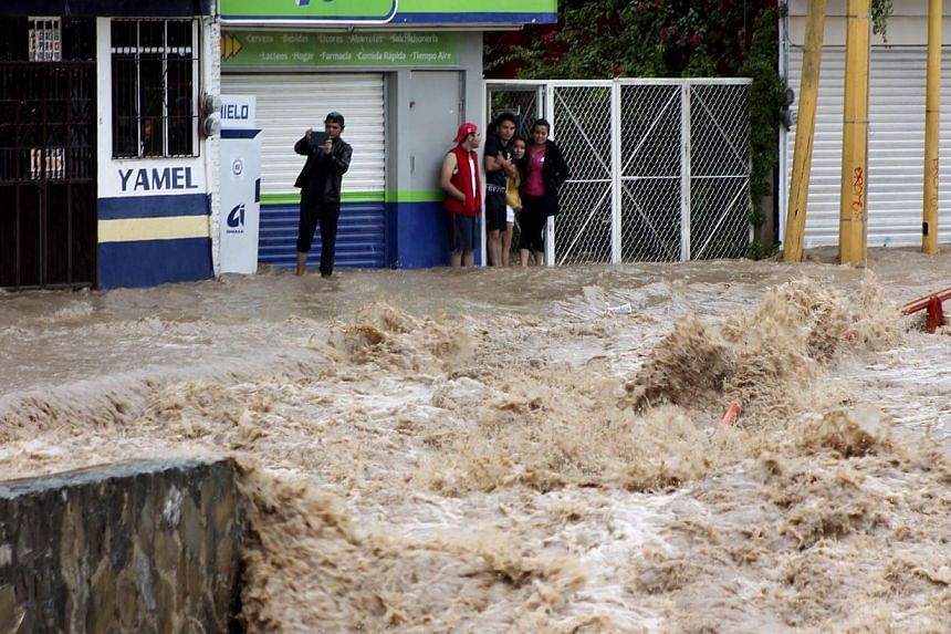 Residents stand in flooded streets in Chilpancingo, Guerrero state, Mexico following tropical storm Manuel which landed in the Pacifiic coast of Mexico on Sep 15, 2013. -- PHOTO: AP